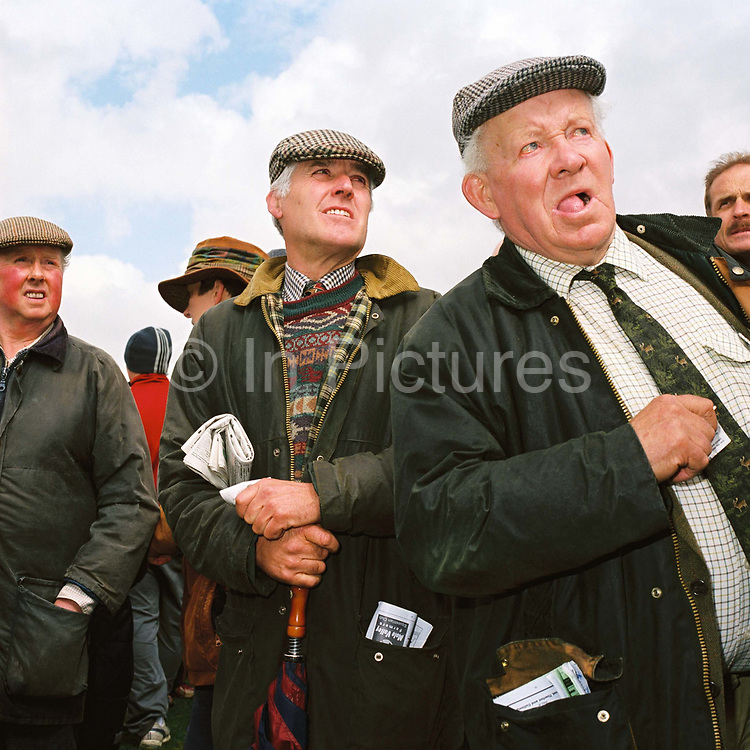 Male spectators wearing Barbour jackets and flat caps by the betting kiosks at the Tiverton Staghounds point-to-point steeplechases at Bratton Down, Barnstaple, Devon, UK. Fundraiser for the Devon and Somerset Staghounds.