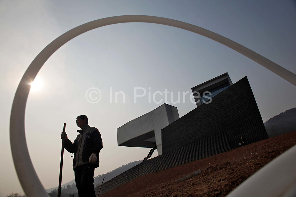 A worker stands near Steven Holl's Sifen Art Museum, which is still under construction at the CIPEA park in Nanjing, China on 04 March, 2011.