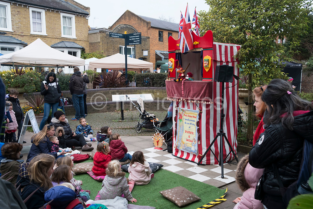 Children watch a Punch and Judy show in Twickenham in London, England, United Kingdom. Punch and Judy is a traditional, popular, and usually violent puppet show featuring Pulcinella, Mr. Punch, and his wife Judy. The performance consists of a sequence of short scenes, each depicting an interaction between two characters, most typically Mr. Punch and one other character who usually falls victim to Judys club. It is often associated with traditional British seaside culture.