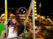 """NEWS&GUIDE PHOTO / PRICE CHAMBERS.Brian Avinger kisses girlfriend Dawn Smith on the ferris wheel at the Teton County Fair carnival on Saturday night. """"I promised her I'd take her on it,"""" said Avinger. Smith said she enjoys the ferris wheel because, """"You can make out on it."""""""