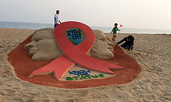 November 30, 2018 - Bhubaneswar, India - Indian sand artist Manas Sahoo creating a red ribbon at the Bay of Bengal Sea's eastern coast Puri beach, 65 km away from the eastern Indian state Odisha's capital city Bhubaneswar  (Credit Image: © Str/NurPhoto via ZUMA Press)