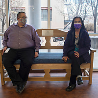 Anthony Dimas Jr., county manager, left, and Marlene Custer, bureau of elections director, right, sit on a bench built by woodworker David Histia III of Zuni to honor former bureau of elections director Rick Palochak at the McKinley County Courthouse in Gallup Thursday.