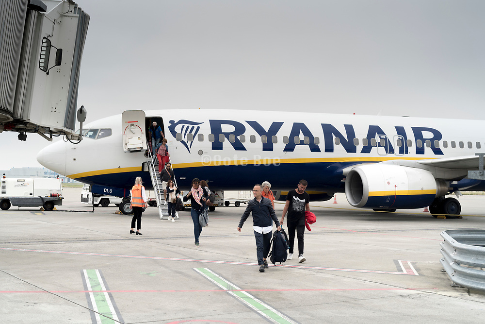 passengers coming from a Ryanair airplane walking towards the airport