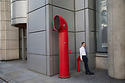 People interact with the red air ducts shaped like funnels, which are part of Vents 88 on London Wall by architect Richard Rogers, appear as strange architectural elements in the City of London, England, United Kingdom. 88 Wood Street is a commercial office tower development in the City of London, England. The architects were Richard Rogers Partnership, now known as Rogers Stirk Harbour + Partners. The building was constructed between 1993 and 2001 and was known as one of the Rogers buildings which placed normally concealed internal elements like ventilation ducts on the outside of the building allowing more internal space.