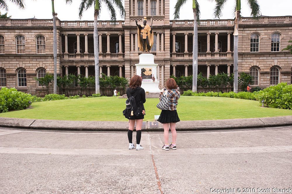 Two toursits in front of the King Kamehameha statue in front of Ali'iolani Hale in Honolulu.
