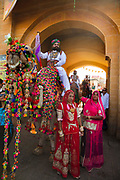 Parading on the backs of camels, Rajasthani men and women in traditional costumes at the Desert Festival on 29th January 2018  in Jaisalmer, Rajasthan, India. It is an annual event that take place in February month in the beautiful city Jaisalmer. It is held in the Hindu month of Magh February, three days prior to the full moon. The men flaunt their moustaches, which go well with the Rajputana spirit that symbolizes the valor and glory of Rajasthan.