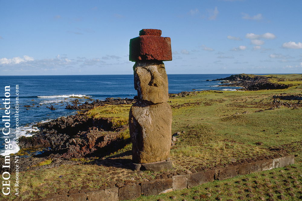"""Capped with a stone hat, a lone """"moai"""" or stone statue stands on an elevated pl atform facing a partially visible stone-studded ceremonial plaza. Its huge volc anic back to the sea, the statue is unable to see the splendor of the Pacific w aves crashing against volcanic rock below.  For more information on """"moai,"""" see No. 17."""