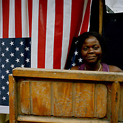 "A Haitian sees the bright side as she sits outside her shelter erected opposite the Palace in Cham De Mars. The  choice of cloth for her shack is symbolic and many Haitians are grateful for the aid and support from the US. some  commentators, however,  believe the relationship with the US two hundred miles away,  is what needs to be looked at if things are to improve. One Haitian, Jocelyn, tells me:  ""They (The American government)  take with one hand and give with the other.  They swamped Haiti with cheap rice imports putting farmers out of business and forcing them into the capital's slums where they have been aid dependent ever since"""