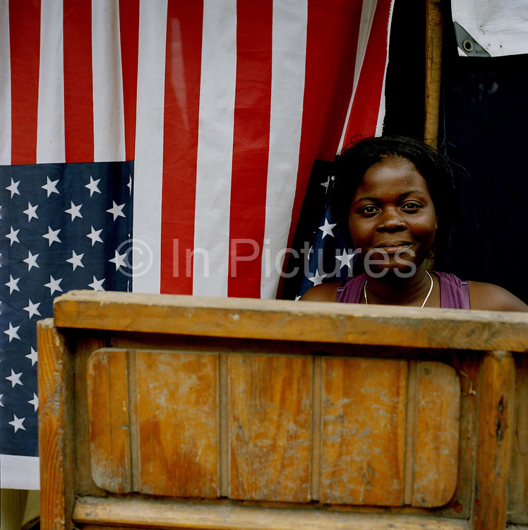 """A Haitian sees the bright side as she sits outside her shelter erected opposite the Palace in Cham De Mars. The  choice of cloth for her shack is symbolic and many Haitians are grateful for the aid and support from the US. some  commentators, however,  believe the relationship with the US two hundred miles away,  is what needs to be looked at if things are to improve. One Haitian, Jocelyn, tells me:  """"They (The American government)  take with one hand and give with the other.  They swamped Haiti with cheap rice imports putting farmers out of business and forcing them into the capital's slums where they have been aid dependent ever since"""""""