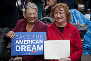 "Two senior women hold signs: ""Save the American dream"" and ""Congress hear us now""."