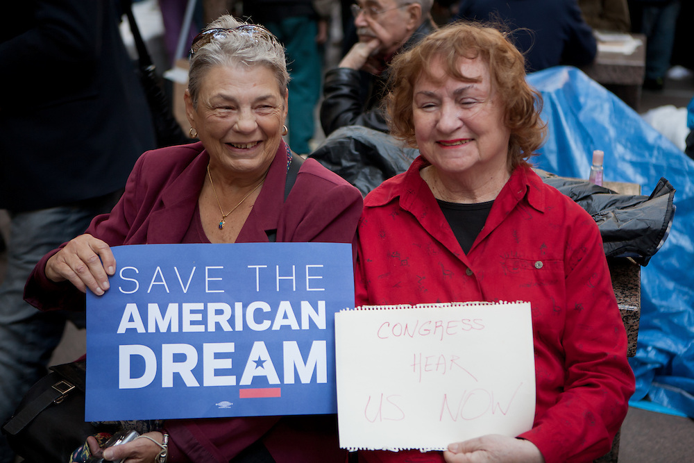 """Two senior women hold signs: """"Save the American dream"""" and """"Congress hear us now""""."""