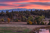 A colorful sunset fills the sky as seen from Welch Ranch Recreation Area. The Tongue River flows is in the lower right and the snow capped Bighorn Mountains are in the background.