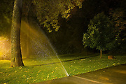 A sprinkler sprays water against trees on the University of Colorado campus in Boulder, Colorado.