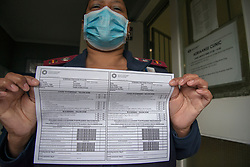 Clinic Manager Marilyn Jantjies holds up a screening sheet for TB and COVID-19 at the entrance of the Adriaanse Clinic in Elsies River, Cape Town, Monday, July 13, 2020. All patients are screened verbally for COVID-19 at the clinic door, and are asked to go to the hospital for a test if they screen positive. Although many health facilities in the area have experienced their health workers contracting COVID-19, Jantjies says nobody on her staff has yet taken ill. PHOTO: EVA-LOTTA JANSSON