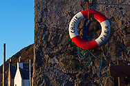 Crovie Pier, Scotland. Lifebouy on wall. Cottages in background.