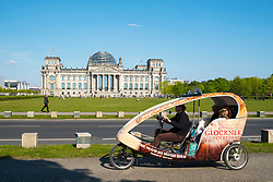 Tourist sightseeing rickshaw in front of the Reichstag in Berlin, Germany