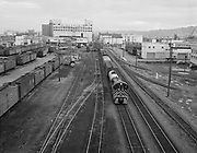 """9969-540616-1. """"Portland skyline at evening. Railroad switch train. June 16, 1954"""" Locomotive in train yard, looking south from the Burnside Bridge. In the foreground is the land from Ankeny to Oak between Water and Second avenue."""