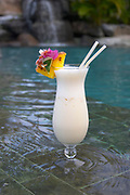 Tropical drink by pool with waterfall in background,  Bora Bora, Society Islands