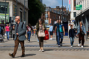 People, some with shopping bags, walk down the city centres main high street on 2nd September, 2021 in Leeds, United Kingdom. Despite a rise in footfall across the UKs high streets, new data has shown more than 8,700 chain stores have closed permanently, with the Covid-19 pandemic seeing consumer habits shifting in favour of shopping online or locally.