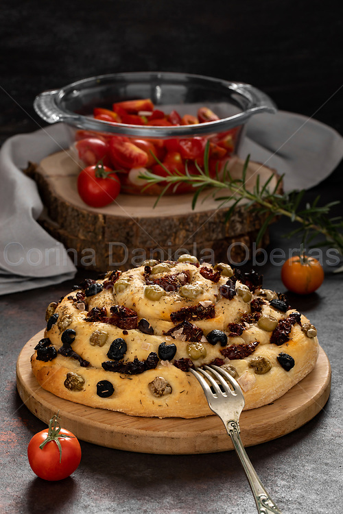 Type of rolled bread with dried tomatoes, capers and olives.
