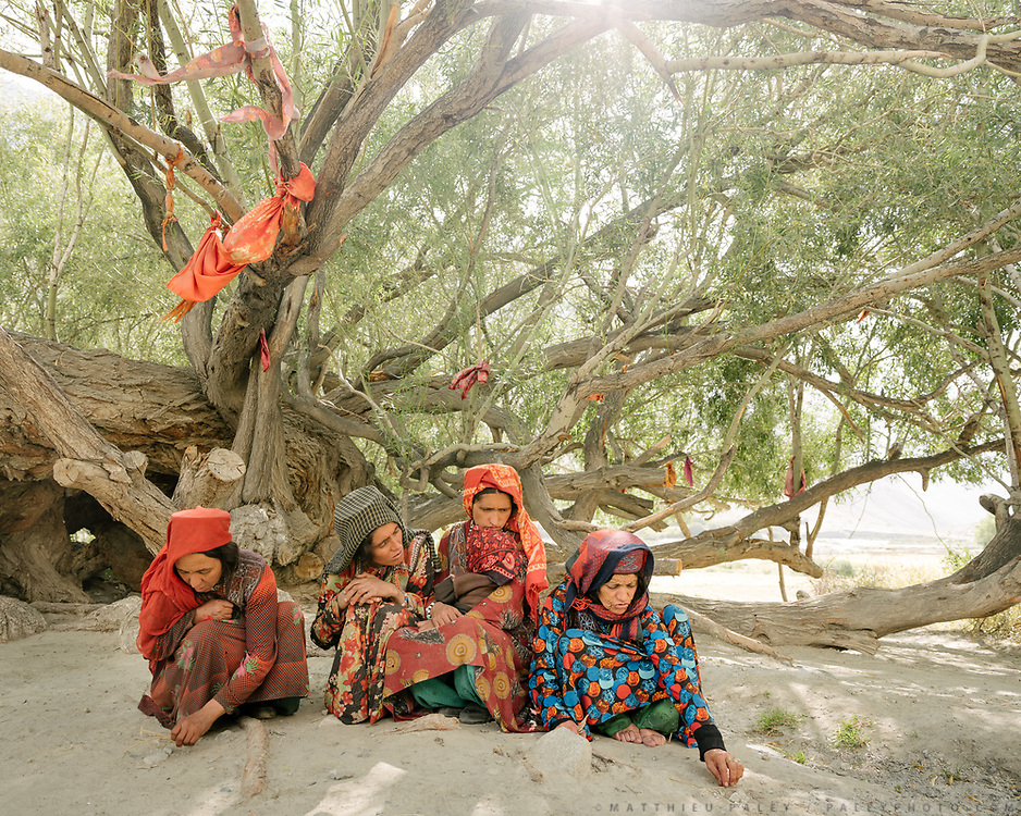 """These women are talking in the shade of this + - 400 old tree. It's one of the many holy places in the Wakhan, called Ostone. They are cleaning the floor of the small pieces of wood that fell overnight and then putting them away behind them, at the base of the tree. Although they are muslims, many of their religious practices show the herirage pf previous beliefs like animism, fire worshipping, Buddhism etc This shrine named """"Saïd Brom"""". In the village of Kipkut. The traditional life of the Wakhi people, in the Wakhan corridor, amongst the Pamir mountains."""