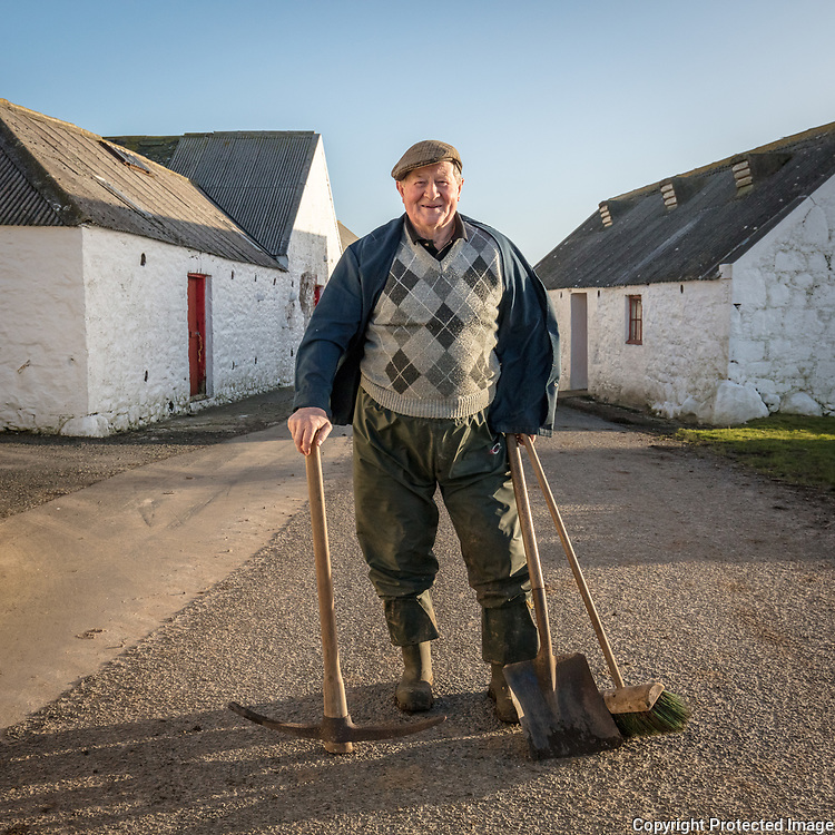"""Hughes of Knockencule Farm on the way to feed his cows. <br /> There are a handful of derelict crofts on his land that once housed seven people that used to work with him. Today he manages the farm mostly alone """"All the young ones leave after school now"""". The Rhins, Dumfries and Galloway, Scotland."""
