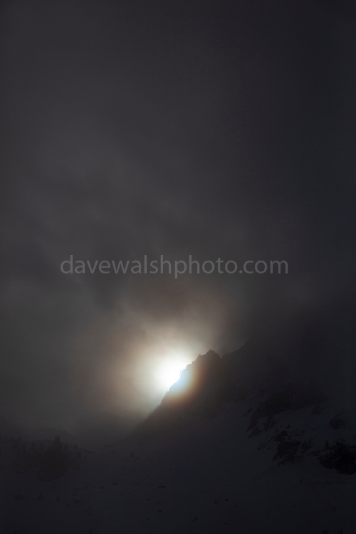 Sunlight filters over a mountain peak and through the fog. La Mongie, ski resort, in a thick fog.