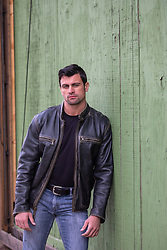 man in a leather jacket against a wall