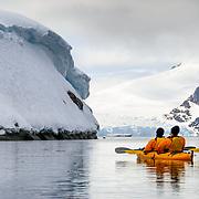 A pair of kayakers in a tandem kayak float through calm waters at Petermann Island in Antarctica.