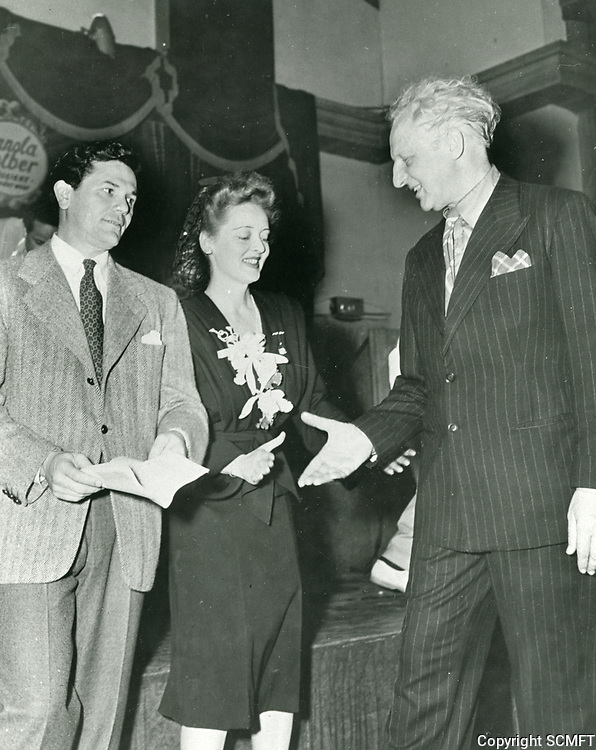 10/43 Hollywood Canteen co-founders, John Garfield and Bette Davis greet conductor, Leopold Stokowski during the Canteen first birthday