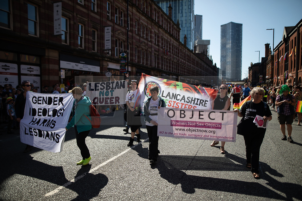 """© Licensed to London News Pictures . 24/08/2019. Manchester, UK. A protest by Lesbians opposed to some concepts of Transgender Identity , referred to as """" TERFS """" blocks the parade . The 2019 Manchester Gay Pride parade through the city centre , with a Space and Science Fiction theme . Manchester's Gay Pride festival , which is the largest of its type in Europe , celebrates LGBTQ+ life . Photo credit: Joel Goodman/LNP"""