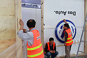 Workers stand by a Volkswagen AG logo while preparing the set for the China ( Guangzhou) International Automobile Exhibition in Guangzhou, Guangdong Province, China, on Monday, Nov. 21, 2011. Despite signs of slowing, China remains the largest and fastest growing market for international car makers, especially in the luxury sector.
