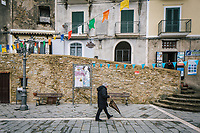 CASTELLABATE, ITALY - 14 FEBRUARY 2018:  A man walks in the main square in Castellabate, Italy, on February 14th 2018.<br /> <br /> Castellabate is part of the electoral college of Agropoli, in the Campania region (southern Italy) in which Franco Alfieri (Democratic Party, PD, Partito Democratico), politically active for the past 30 years, is running agains the 28-years old Alessia d'Alessandro (Five Stars Movement, M5S, Movimento 5 Stelle).<br /> <br /> The 2018 Italian general election is due to be held on 4 March 2018 after the Italian Parliament was dissolved by President Sergio Mattarella on 28 December 2017.<br /> Voters will elect the 630 members of the Chamber of Deputies and the 315 elective members of the Senate of the Republic for the 18th legislature of the Republic of Italy, since 1948.Santa<br /> <br /> The 2018 Italian general election is due to be held on 4 March 2018 after the Italian Parliament was dissolved by President Sergio Mattarella on 28 December 2017.<br /> Voters will elect the 630 members of the Chamber of Deputies and the 315 elective members of the Senate of the Republic for the 18th legislature of the Republic of Italy, since 1948.