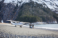 Zack Tappan, cheif pilot at Homer Air, and his flightseers stand beside the cessna 206 bushplane that brought them to a remote beach in the Kenai Fjords during a flightsee adventure from Homer, Alaska.