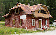 Bicyclists rest by an old red hotel marked Km.119.000 on Strada Statale 51, about 20 minutes north of Cortina d'Ampezzo, in the Province of Belluno, Veneto region, Italy, Europe.