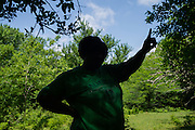 """UNIONTOWN, AL – MAY 21, 2015: Esther Calhoun, a native of Uniontown, points to the location where contaminated water from a lagoon flows into Freetown Creek. """"It's a shame this is happening,"""" Calhoun said. """"If we were a bigger town people would care about what was going on. But being in the black belt, nobody cares."""" Despite the prevalence of chalky clay soil throughout much of the Black Belt, spray fields have been utilized as a primary sewage treatment method. The inability of the sewage water to percolate through the soil often leads to problems of overflow and contamination of the area's water supply."""