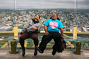 Jessica Longboy and Kalei Amion, who are visiting Seattle from Hawaii, laugh as they nervously sit back against the new glass walls of the Space Needle observation deck, Wednesday, May 30, 2018.  The new angled glass benches and barrier walls give visitors a thrill.  (