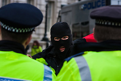 Whitehall, London, April 4th 2015. As PEGIDA UK holds a poorly attended rally on Whitehall, scores of police are called in to contain counter protesters from various London anti-fascist movements. PICTURED: A masked anti-fascist counter-protester taunts police officers