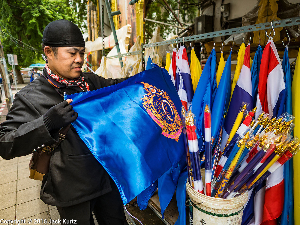 10 AUGUST 2016 - BANGKOK, THAILAND: A man buys the blue royal flag of Queen Sirikit of Thailand. Thais are preparing for the Queen's birthday. Queen Sirikit of Thailand, was born Mom Rajawongse Sirikit Kitiyakara on 12 August 1932. She married  Bhumibol Adulyadej, King of Thailand (Rama IX) in 1950. He is the longest serving monarch in the world and she is longest serving consort of a monarch. Her birthday, like the King's Birthday (which falls on Dec. 5),  is a national holiday in Thailand. Her birthday, August 12, is also celebrated as Mothers' Day in Thailand. Thais hang portraits of Queen Sirikit in their homes and fly her royal flag on her birthday.        PHOTO BY JACK KURTZ