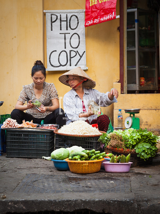© Rob Arnold.  15/04/2013. Hanoi, Vietnam. Two women selling various products including bean sprouts, cucumbers, spring onions, meat and a photocopy service. Photo credit : Rob Arnold