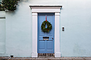 The colorful wooden door on a historic home decorated with a Christmas wreath on Tradd Street in Charleston, South Carolina.