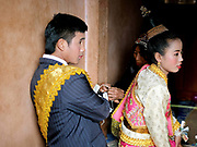 An Akha couple dressed in Lao style clothing at their wedding Baci in Ban Lang Pa village, Luang Namtha province, Lao PDR. Baci is a Buddhist ceremony to celebrate a special event such as a marriage.