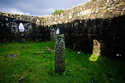 The upright remains of a Pennygowan Cemetery (Caol Fhaoileann), Salen Isle of Mull, Scotland. Within the chapel, erected on a modern base, is the lower part of a cross-shaft 1.33m high above ground. On the front there has been a Crucifix; below this a large plant scroll terminates in a griffin. At the foot is a galley with sail set. This cross dates to between 1500 and 1560 and the ruined chapel is probably of early 13th century date. No medieval references to it have been identified, and its dedication is unknown though it is referred to both as a 'Chappell' and as a 'paroach'. The building may already have been derelict at this period, although the earliest evidence of its condition dates from 1787 when it was shown as 'an old kirk' on a map of Torosay parish.