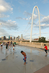 Kids playing in water fountains on Continental Avenue Bridge with Margaret Hunt Hill Bridge in background, Trinity River, Dallas, Texas, USA.