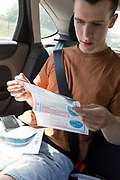 A young man in his twenties reads printed instructions after inserting a swab into his mouth to reach his tonsils and into his nasal passage from the rear seat of a car for a self-administered Coronavirus (COVID-19) test in south London. There are four steps to the self-administered Covid-19 test (inserting a swab into the nose and throat) which the public works through in their car, windows up and all communications with army personnel via phone, in a south London leisure centre, on 2nd June 2020, in London, England. The kit provided consists of a booklet, plastic bag, swab, vial, bar codes and a sealable biohazard bag. The swab sample is taken from the back of the throat and nasal passage with the contents sealed and returned to soldiers through a narrow window. The whole process takes between 5-10mins with results available with 48hrs.