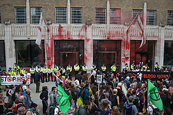 Environmental activists from Extinction Rebellion stand in front of the Guildhall after spraying it with blood-red paint during a Blood Money March through the City of London on 27th August 2021 in London, United Kingdom. Extinction Rebellion were intending to highlight financial institutions funding fossil fuel projects, especially in the Global South, as well as law firms and institutions which facilitate them, whilst calling on the UK government to cease all new fossil fuel investment with immediate effect.