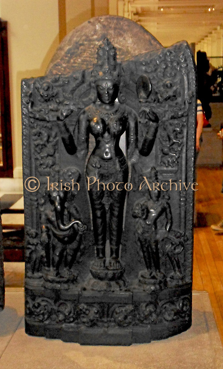 Lalita between Ganesa and Karttikeya, 11th century, Eastern India.  The great goddess stands between her two sons who are flanked by fly-whisk bearers.