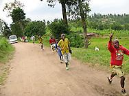 Rwanda- Rwandan school children run down a road ahead of a bus in a rural area between Nyanza and Butare, Rwanda.