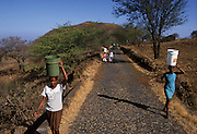 Women carrying water on the road. The Dry is the main problem in Cape Verde islands as most of the land remains unproductive due to arid soils.