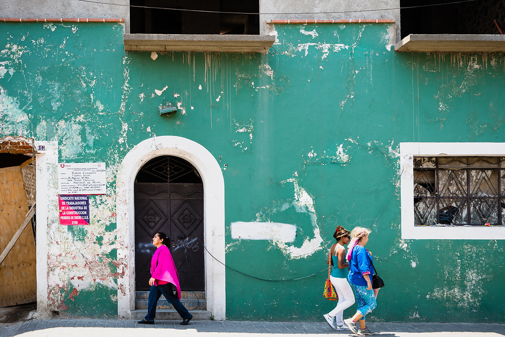 People walking past a colourful wall in Cholula, Mexico